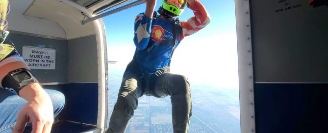licensed skydiver hangs out of plane ready to jump